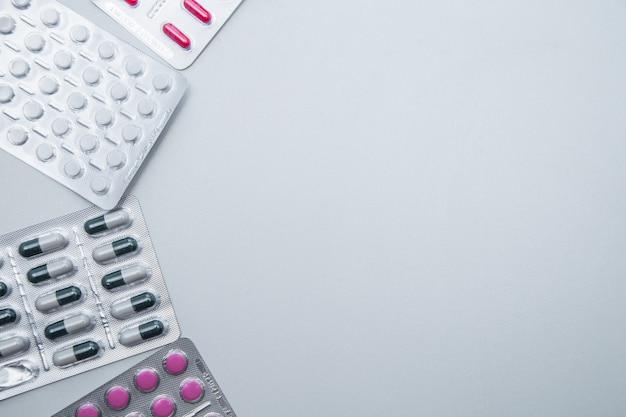 Таблетки и капсулы в упаковке лежат сбоку на белом фоне с местом для текста в т ...