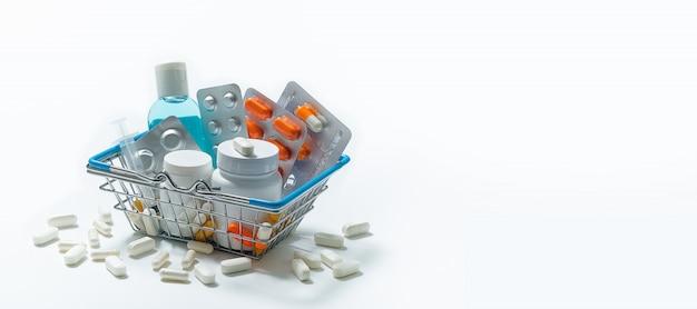 タブレットと白い背景の上のショッピングカートの薬。薬と薬局のコンセプト。
