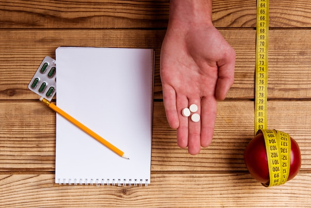 Tablets on hand, notepad and pencil and tape on table.