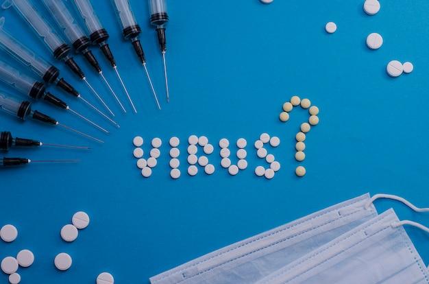 Таблетки выложены со словом вирус с вопросительным знаком и шприцы на голубом фоне. каковы симптомы вируса? вопросы распространения и лечения.