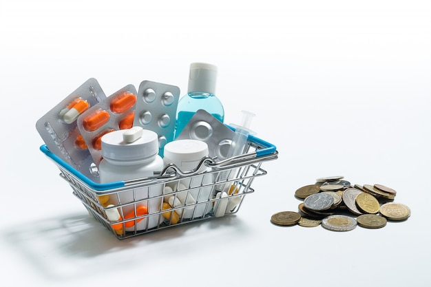 Tablets and medications in the shopping cart on a white surface. next to the coins of all countries of the world.