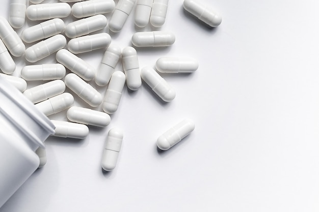 Tablets and medications on a white surface.