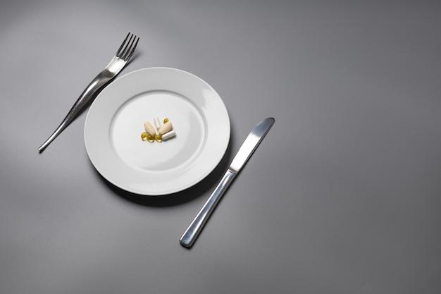 Таблетки на тарелке в качестве еды