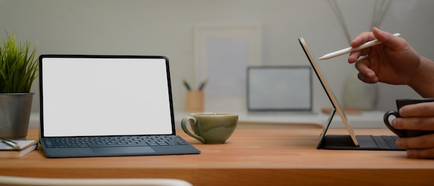Tablets with white screens and cups of coffee