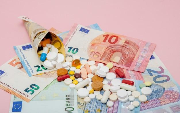 Таблетки, завернутые в евро с банкнотами евро на розовом фоне.