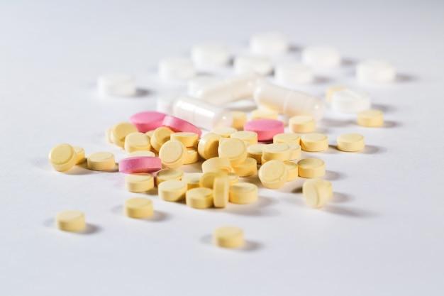 Таблетки. желтые и розовые таблетки на белом фоне.
