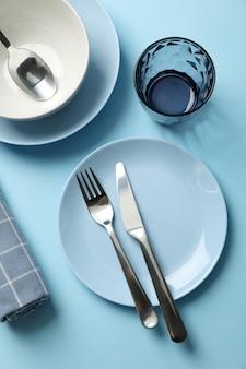 Посуда и столовые приборы на синем фоне, вид сверху