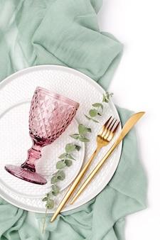 お祝いのテーブルを提供するための食器と装飾。プレート、ワイングラス、カトラリー、白い背景に灰色の装飾的なテキスタイル。