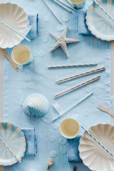 Посуда и украшения для сервировки стола в морском стиле. элегантные тарелки, бумажные стаканчики, соломинки и столовые приборы. день рождения или концепция детского душа мальчика.