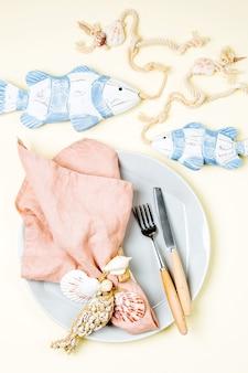 축제 테이블을 제공하는 식기 및 바다 장식 접시 와인 잔 및 수저