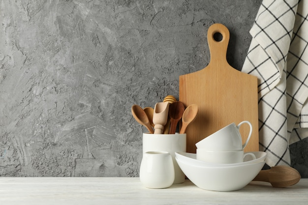 Посуда, столовые приборы и деревянная доска на белом столе на сером фоне, место для текста