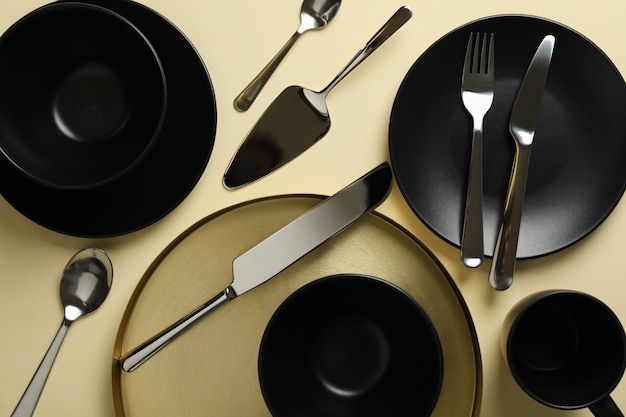 Tableware and cutlery on beige background, top view
