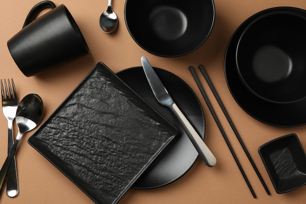 Tableware and cutlery on craft background, top view