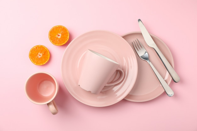 Tableware and cutlery on pink background, top view