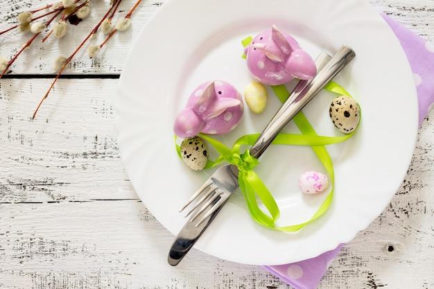 Посуда день счастливой пасхи - тарелка, нож, вилка, вид сверху.