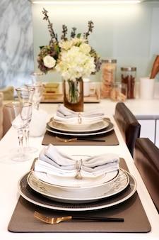 저녁 식사용 식기는 2개의 와인 잔, 나이프와 포크가 포함된 3가지 크기의 접시, 주방의 카운터에 놓인 냅킨 2개로 구성됩니다.