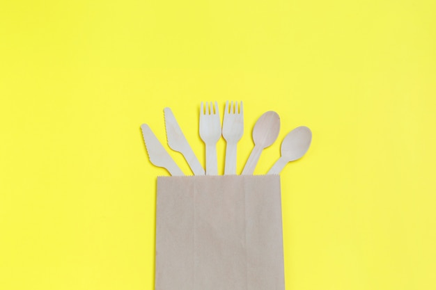 Tableware from natural materials, wooden spoons, knives, and forks in paper bag on yellow background.