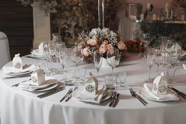 아늑한 인테리어의 레스토랑에서 저녁 식사로 제공되는 식기 잔, 꽃 포크, 나이프