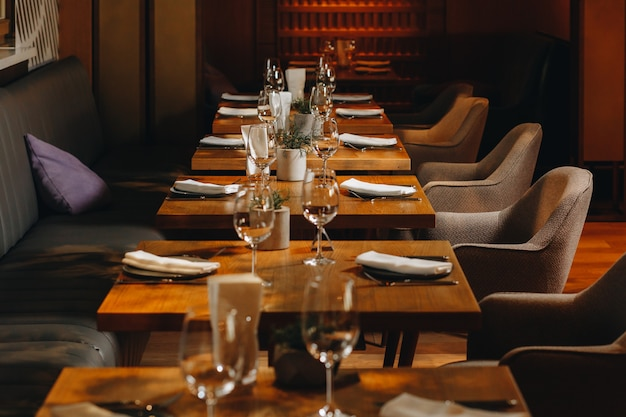 Посуда стаканы, вилка для цветов, нож подаются на ужин в ресторане с уютным интерьером