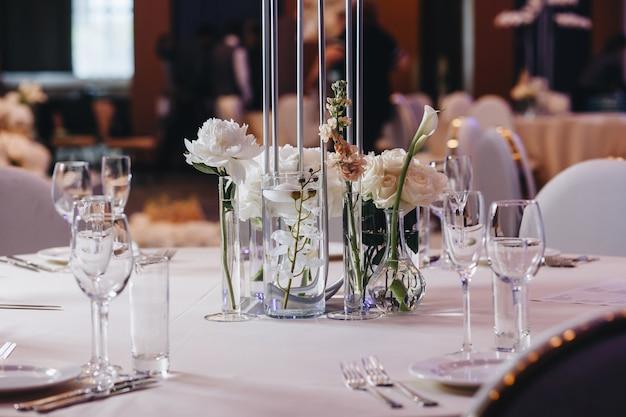 아늑한 인테리어의 레스토랑에서 저녁 식사로 제공되는 식기 안경 꽃 포크 나이프