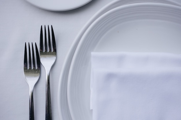 아늑한 인테리어가 있는 레스토랑에서 저녁 식사로 제공되는 식기 유리 꽃 포크 나이프
