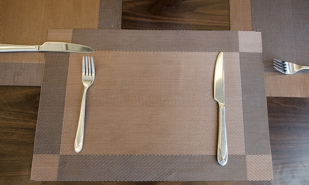 Tableware knife and fork with table cloth on wood table