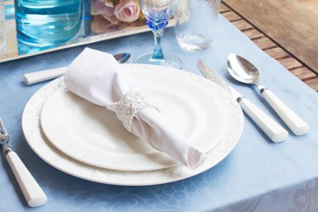 青いテーブルクロスに白いプレート、カップ、utencilsの食器セット