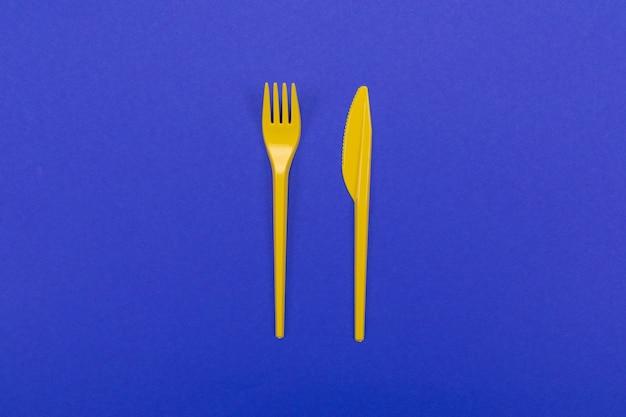 Набор посуды из желтой пластиковой вилки и ножа, изолированных на синем фоне