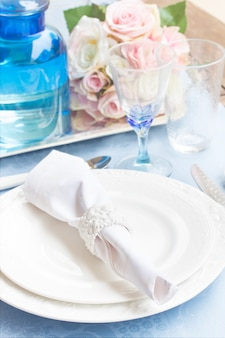 Tableware set of plates, cups, utencils and flowers