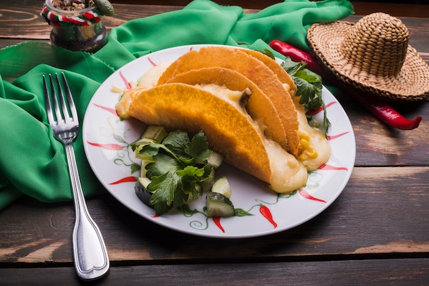 냅킨과 칠리와 솜브레로 근처 접시에 야채 중 타코