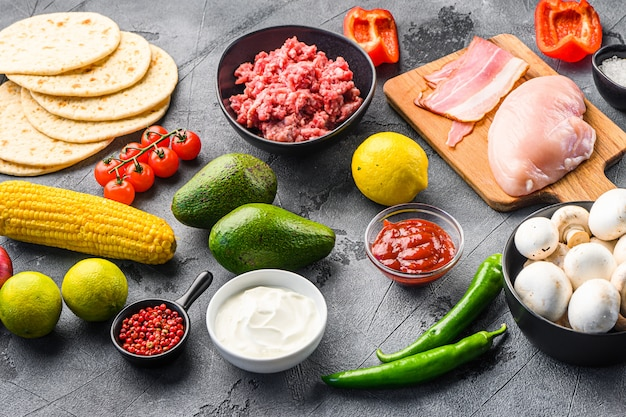 Taco ingredients homemade cooking with vegetables and chicken beef and pork meat, corn, mushrooms