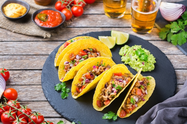 Taco shell ellow corn tortilla chips nachos with ground beef, mince, guacamole, red hot jalapeno chili salsa and cheese sauce with tequila or beer on a table.