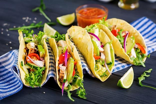 Мексиканские тако с куриным мясом, авокадо, помидорами, огурцами и красным луком. здоровая лепешка. оберните еду. taco