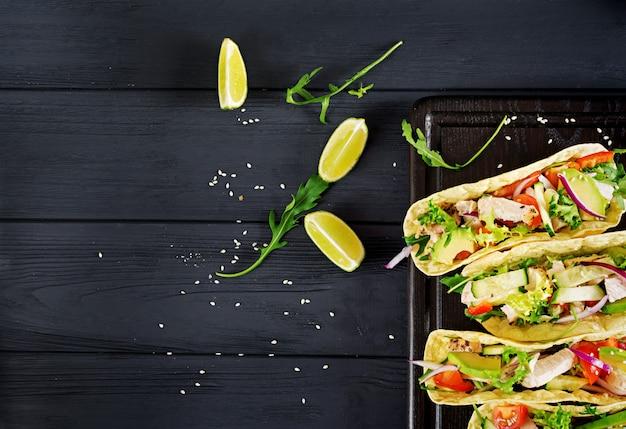 Мексиканские тако с куриным мясом, авокадо, помидорами, огурцами и красным луком. здоровая лепешка. оберните еду. taco. вид сверху