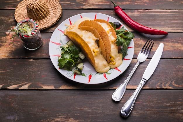 チリとソンブレロの近くの皿に野菜の中でタコス