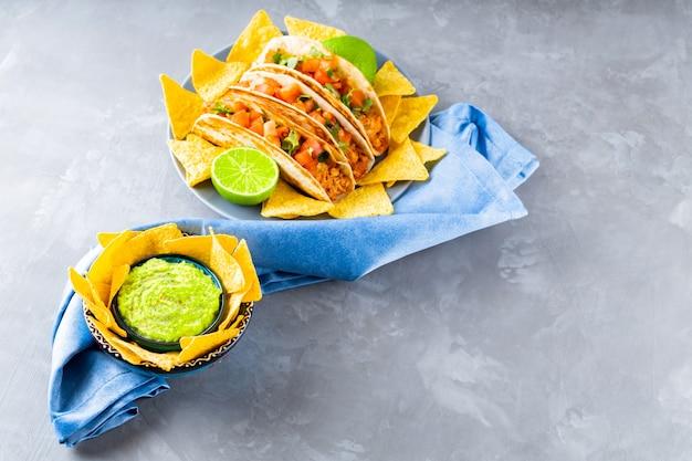 Тако и чипсы из тортильи на сером фоне. мексиканские тако, чипсы начо и соус гуакамоле на синей салфетке. испаноязычная мексиканская кухня. скопируйте пространство. вид сверху