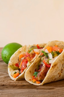 Tacos and lime on wooden table