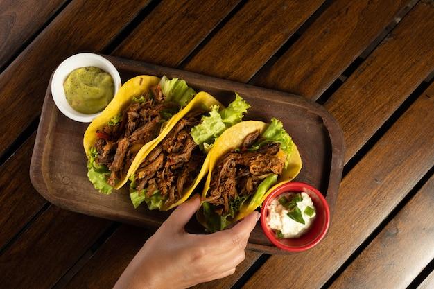 고기 타코. 전통적인 멕시코 음식입니다. 손 잡기 타코.