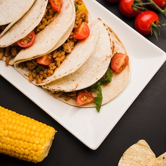Tacos on plate near vegetables