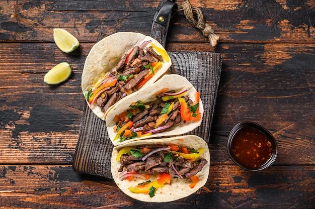 Ракушки тако со свининой, луком, помидорами, сладким перцем и сальсой. мексиканская еда. темный деревянный фон. вид сверху.