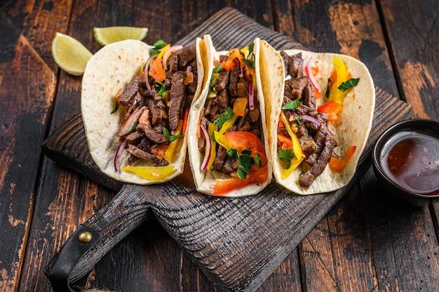 豚肉、玉ねぎ、トマト、ピーマン、サルサのタコス シェル。メキシコ料理。