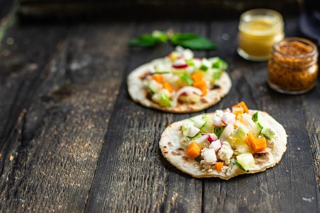 タコス詰め野菜ドネルケバブフラットブレッド野菜タコステーブル上の健康食品食事スナック