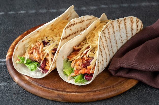 Tacos - traditional mexican dish on wooden board