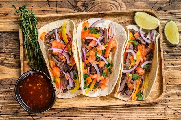 Тако с говядиной, луком, помидорами, сладким перцем и сальсой. мексиканская еда. деревянный фон. вид сверху.