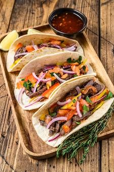 牛肉、玉ねぎ、トマト、ピーマン、サルサのタコス。メキシコ料理。