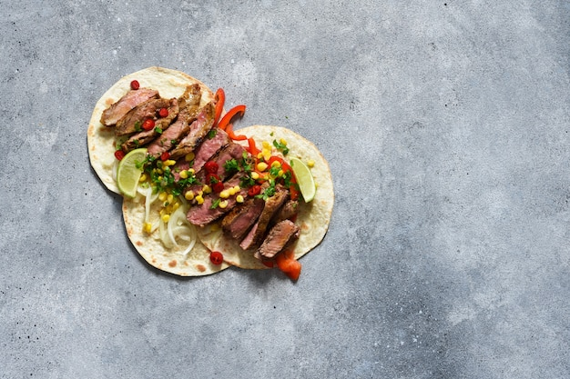 Tacos with beef, pepper and corn with sauce on a concrete background. traditional mexican food.