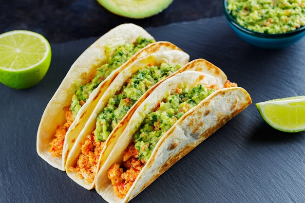 Tacos with chicken and guacamole on a dark background. mexican tacos with fried minced meat on a slate board. traditional dish of mexican cuisine