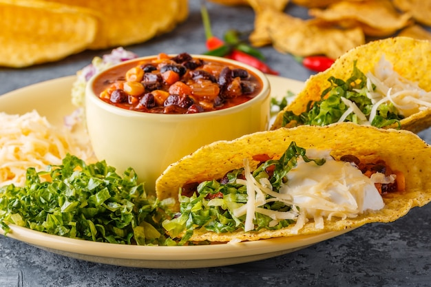 Tacos with chili con carne, salad, cheese and sour cream
