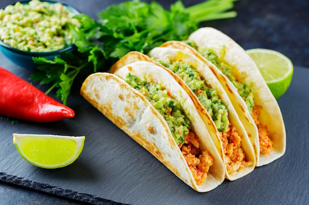 Tacos with fried minced meat and guacamole sauce on a dark background. mexican tacos and ingredients on a slate board. hispanic food