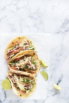 Тако с гуакамоле и салат из капусты подаются с ломтиками лайма на светлом фоне.